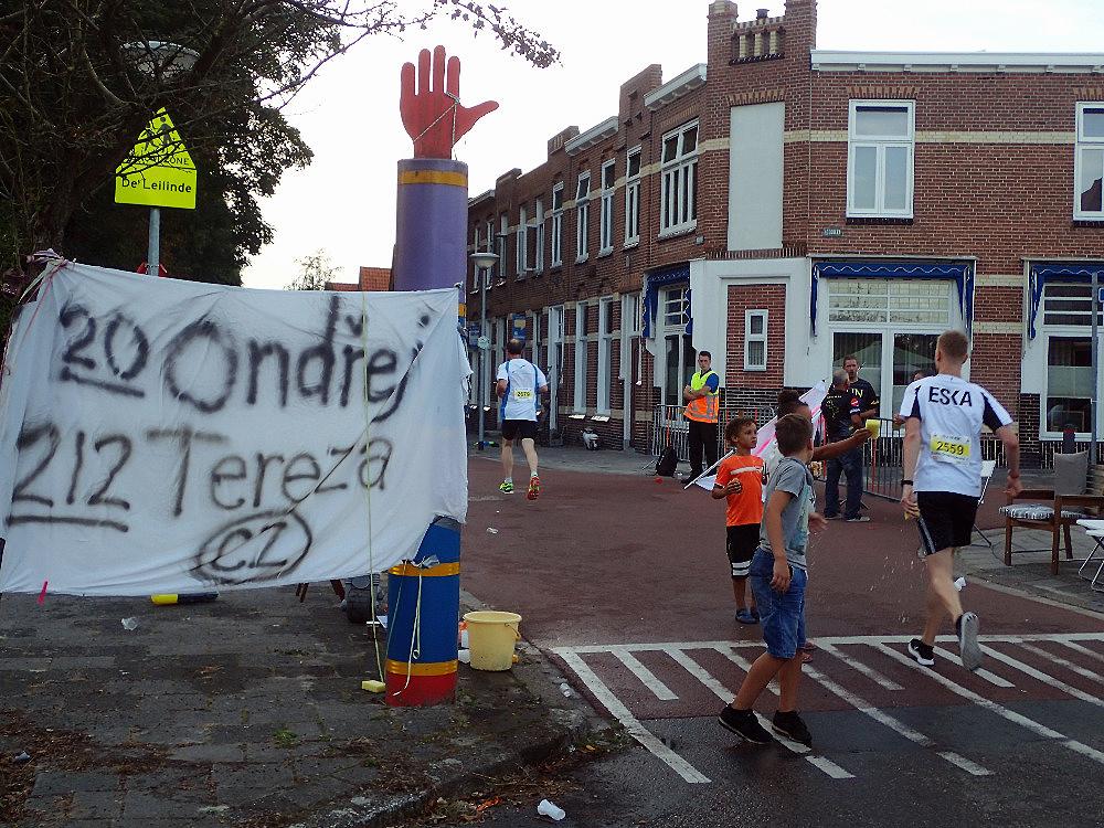 Náš povzbuzovací transparent, v pozadí náš dům. Je vidět, že i zde děti podávaly osvěžovací houbičky závodníkům.