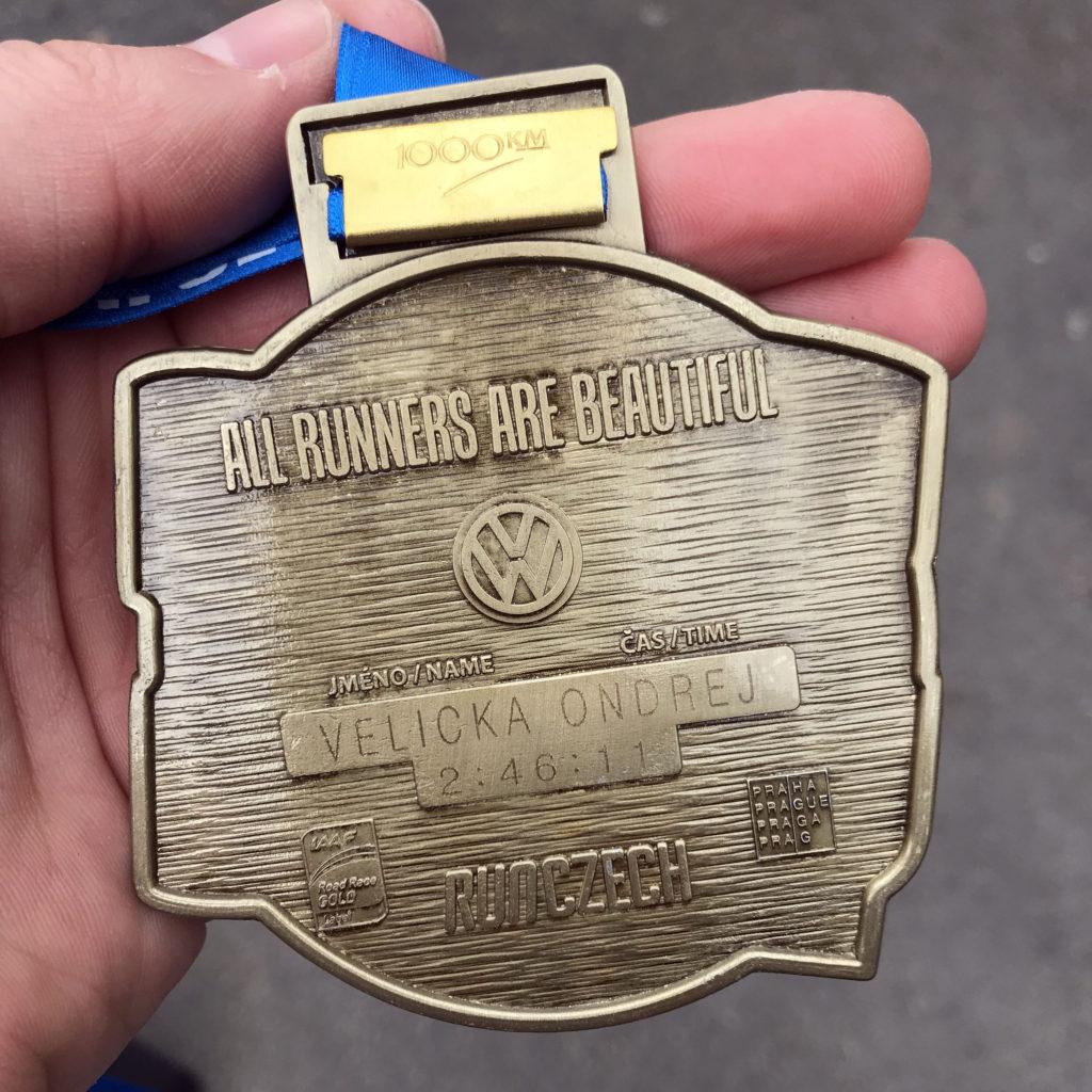 Medaile s vyrytým jménem a časem.