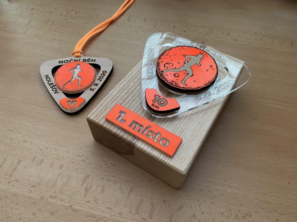 Účastnická medaile s dřevěnou trofejí za vítězství.